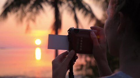 Woman Taking Pictures with Retro Polaroid Camera at Sunset