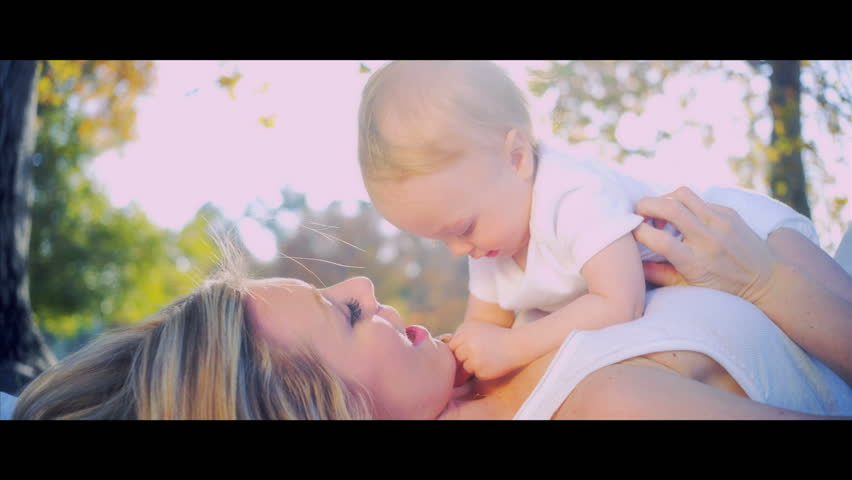 Blonde young mother and baby laughing together while playing outdoors shot in 5K widescreen RED EPIC
