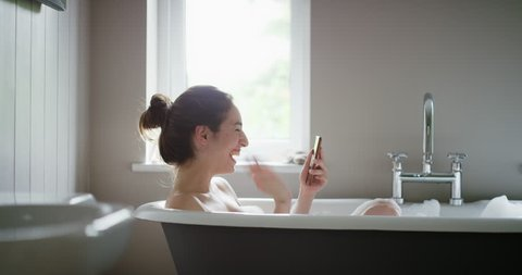 Beauty woman lying in bubble bath having video chat using smartphone webcam chatting to friend at home