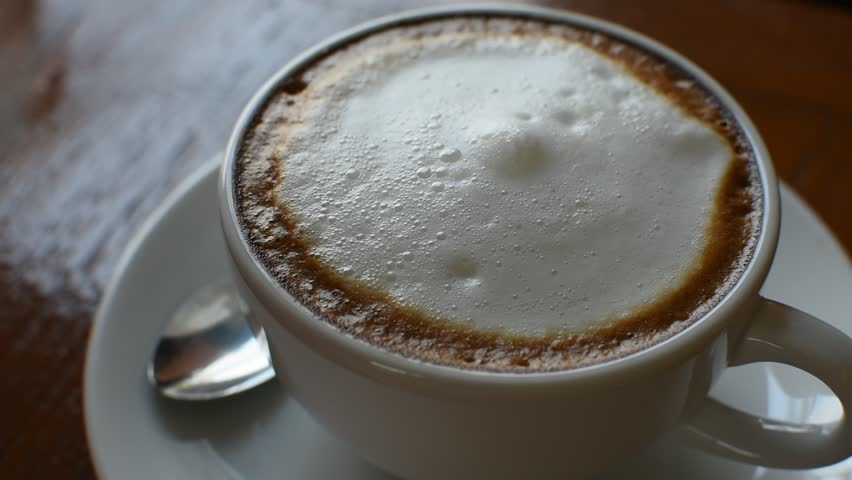 Put to add the red sugar in to hot coffee in white cup on wood table in coffee shop