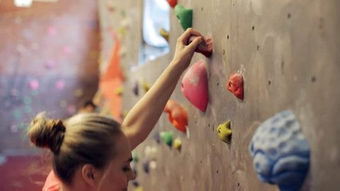 fitness, extreme sport, bouldering, people and healthy lifestyle concept - young woman exercising at indoor climbing gym wall