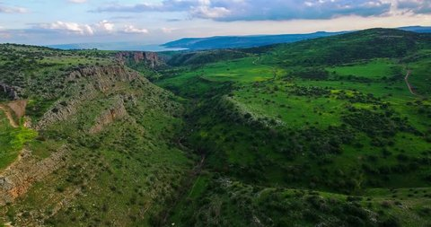Aerial view shot flying over green hills fields and deep valley, with the Sea of Galilee and cloudy skies at the background. Nahal Amud, Israel horizontal and vertical movement.
