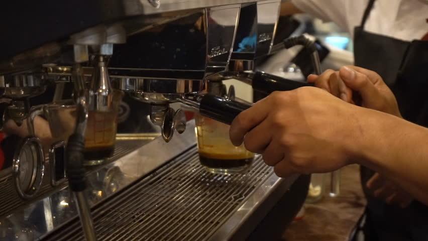 Professional barista prepares a cappuccino in a busy coffee shop