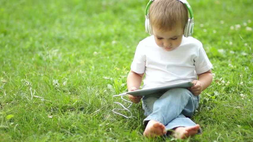 Boy with a tablet PC in headphones outdoors