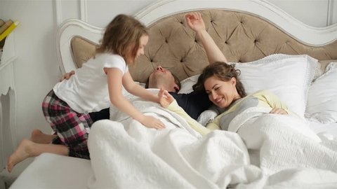 Young Couple is Sleeping Together Hugging in the Bed at Home. Active Little Girl is Waking Her Sleeping Parents up.