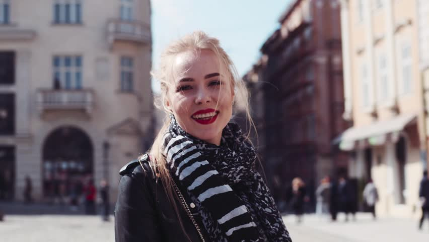 Young attractive woman in a leather jacket, with red lips and blonde ponytail walking in the city center, turns to camera, and shares a bright smile. Casual outfit. Sunny day. Happy moments.
