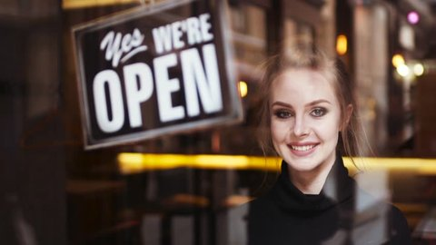 Attractive young blonde woman owner turns sign from close to open and shares a friendly, bright smile to camera. Inside the shop. Being friendly. Successful morning, having a break.