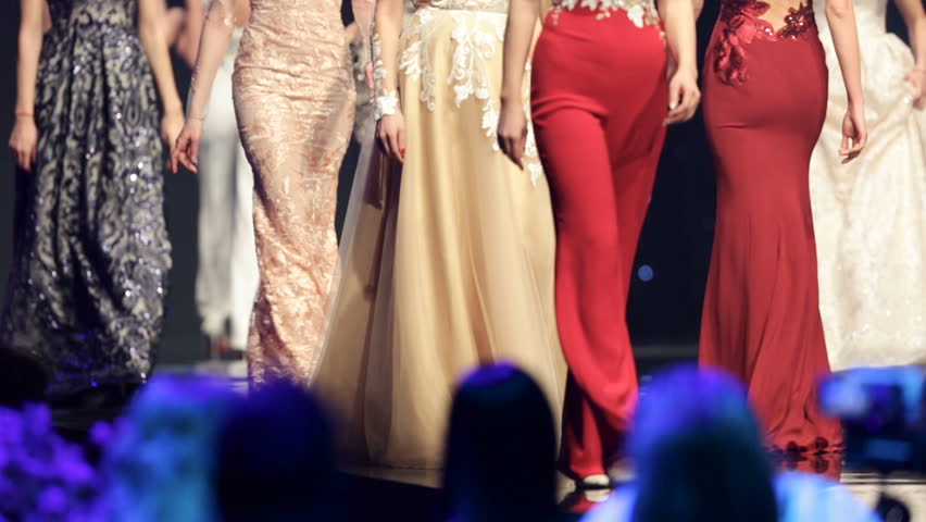 Female models walk the runway in different dresses during a Fashion Show. Fashion catwalk event showing new collection of clothes. Unrecognizable people. Legs only.