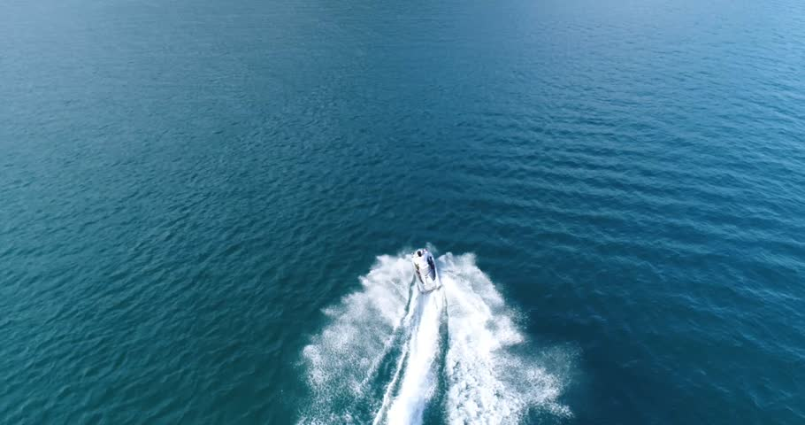 Aerial view of a man riding on a Jet Ski. Following from behind.