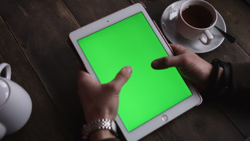 ?loseup hands man touching tablet computer with vertical green screen on the table is tea in a cafe | Shutterstock HD Video #25491524