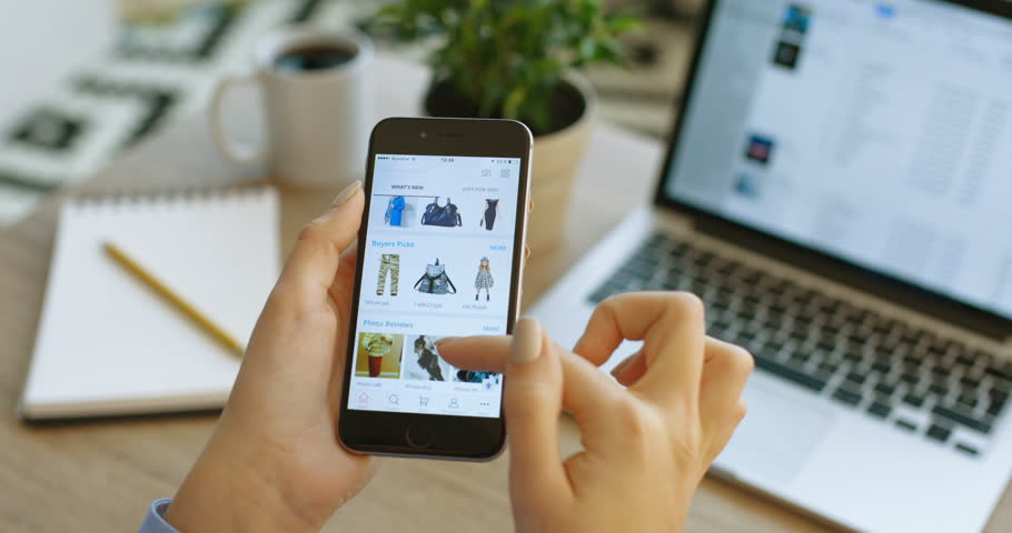 NEW YORK - January 17, 2016: social media. Woman using Aliexpress app on iPhone smart phone. Woman doing online shopping at the AliExpress application, making purchases. Looking for clothes. Hands tapping on
