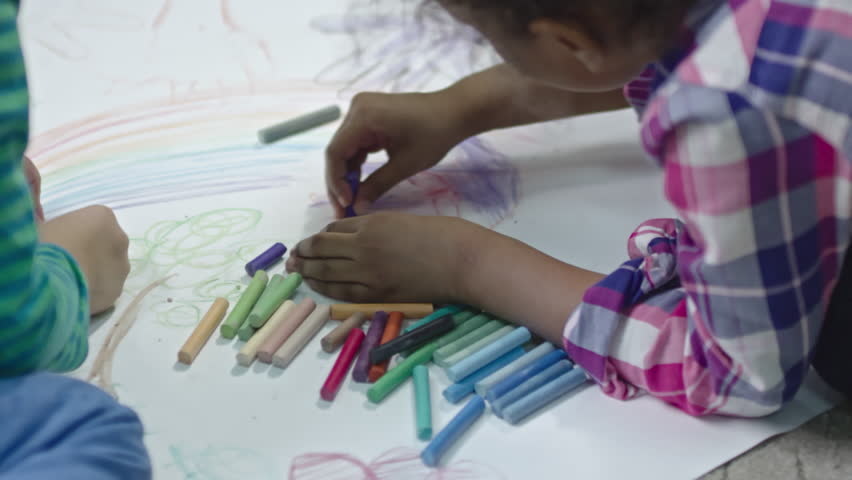 Slow motion shot of little kids sitting on the floor and drawing together on paper with colorful pieces of chalk.   Shutterstock HD Video #25511312