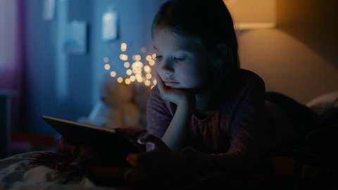 Cute Little Girl in Her Room at Night, Lies on a Bed with Tablet Computer. Her Night Lamp Turned On. Shot on RED EPIC-W 8K Helium Cinema Camera.