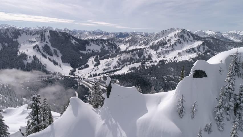 Amazing Aerial Reveal of Highway to Winter Ski Resort with Snowy Mountain Range Peaks | Shutterstock HD Video #25539803
