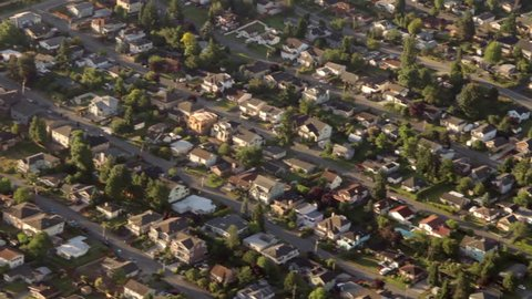 Aerial view from low-flying airplane of suburban neighborhood street and residential blocks
