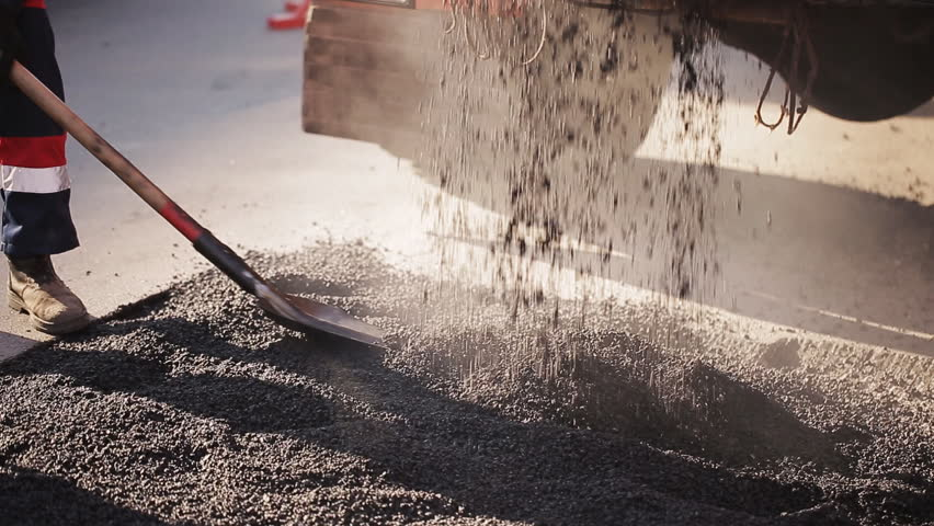Road construction worker leveling asphalt using rake while in the back road roller passing by | Shutterstock HD Video #25549682
