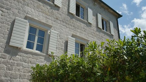 White window shutters. The facade of houses in Montenegro.