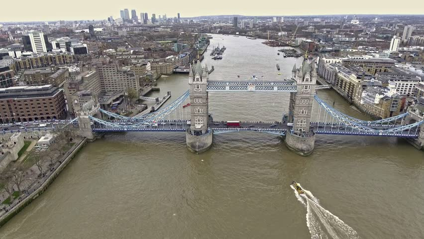 Aerial Shot of Flying Over Tower Bridge and River Thames in London, UK feat. Skyscrapers and Business Office Buildings in the Background with Boats and Car Transportation Vehicles in 4K Ultra HD