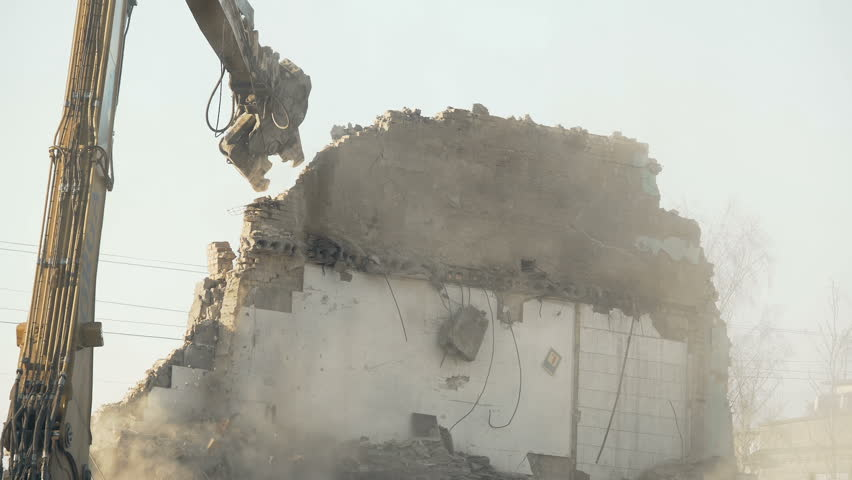 Strong demolition tool crashing old wall, breaking rules, fighting stereotypes