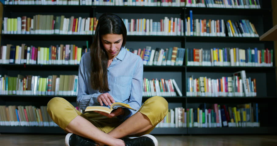 Portrait of a beautiful young woman smiling happy in a library holding books after doing a search and after studying. Concept: educational, portrait, library, and studious. | Shutterstock HD Video #25614251