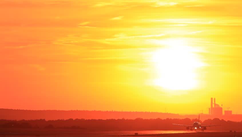 Passenger jet plane taking off runway in sunset