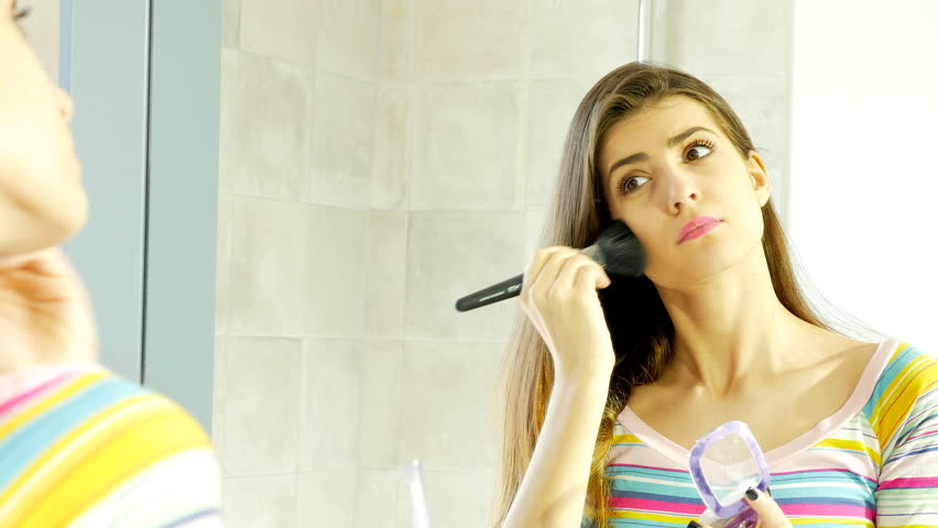 Cute young woman in front of mirror putting makeup in front of mirror