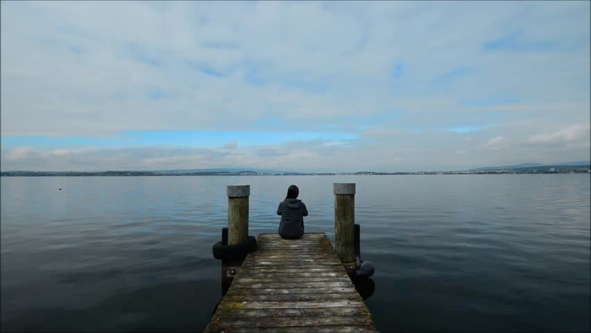 The woman is sitting on the lake shore. Panorama of the lake Zug. Pier in the foreground. Overcast.