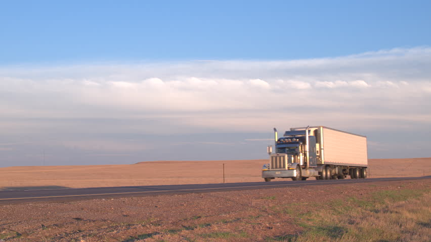 CLOSE UP Freight container semi truck transporting goods driving along the empty interstate highway through the fields in Great Plains, America. Trailer shipping cargo on sunny golden light morning