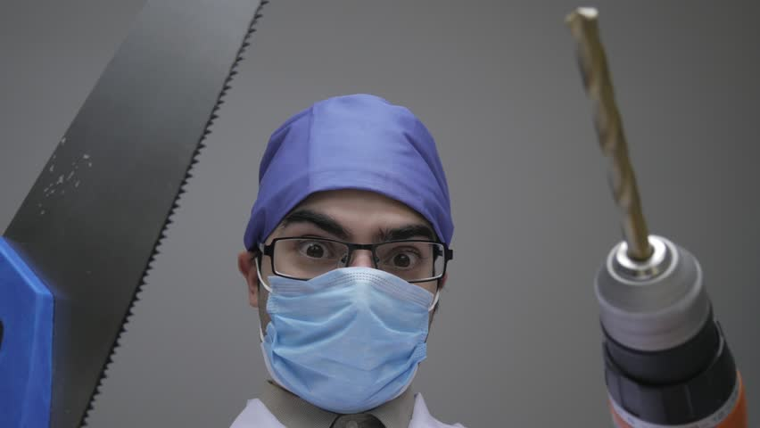 Dentist holding a wood saw and a construction drill while looking scary and dangerous. Personal or patient mouth point of view POV.