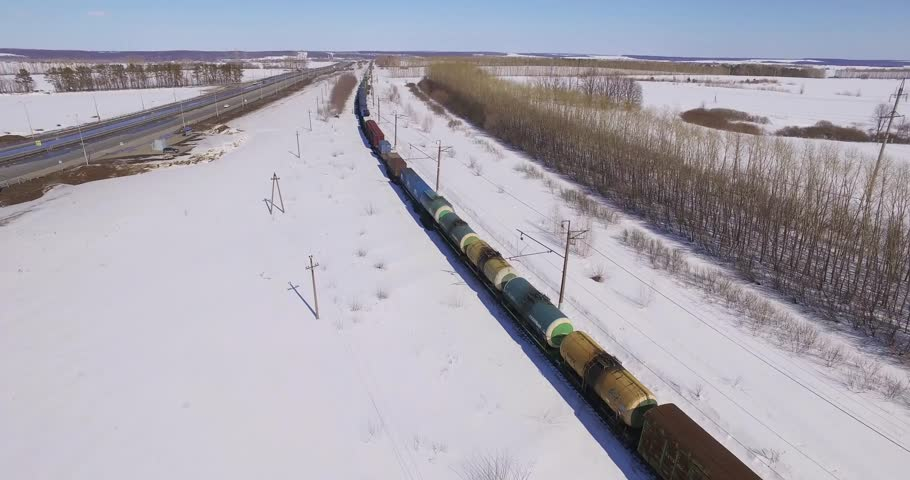 Moving Freight Train Near The Highway At Winter Sunny Day Of Cloudy Sky Russia