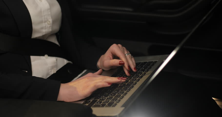 Attractive Business woman works at a laptop in the backseat of car #25674278