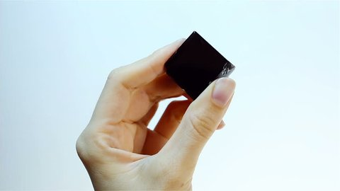 Obsidian is a naturally occurring volcanic glass. Specialist Gemologist Jeweler holding in hand black Obsidian - Sample of gemological set. Semiprecious gem for jewels, esoteric alternative medicine.