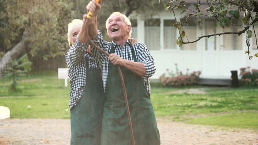 Old couple with garden hose. Cheerful woman and man outdoors.