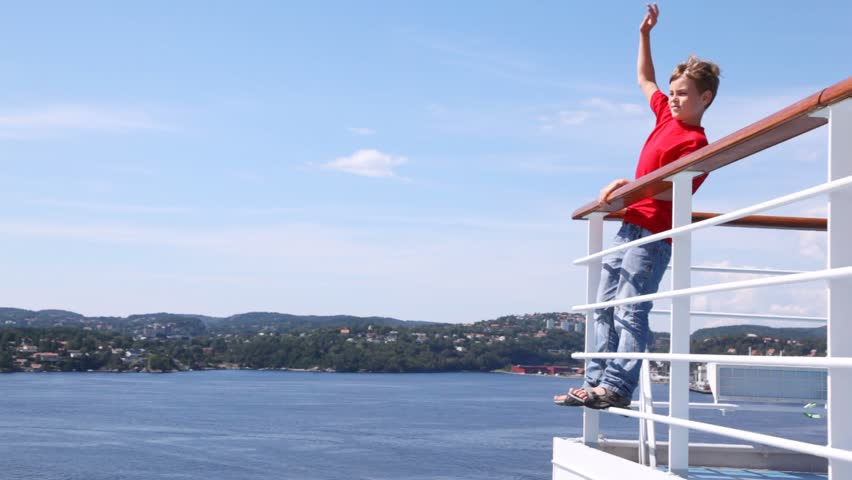 Boy waves greeting by hand standing on ship handrail #2571302