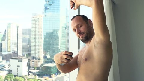 Man applying antiperspirant on armpit by window at home, super slow motion 240fps