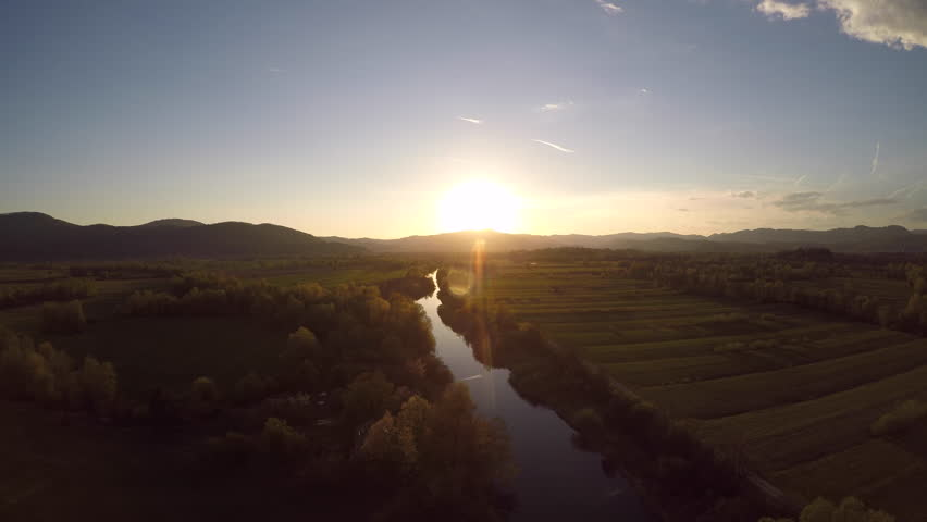 4K: Aerial flight over a river at sunset