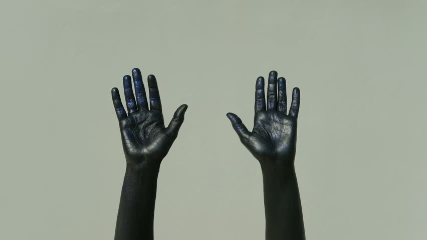 Actor mime with black hands shows gesture goodbye on a gray background. Palms in shiny paint in blue tint flex and unbend fingers slowly. The limbs are stretched and pantomime moves. When parting for