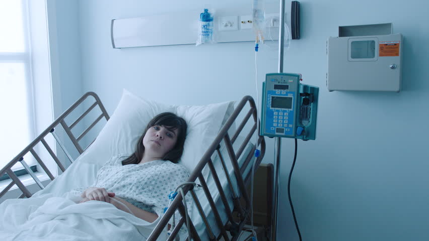 A sick young woman with an IV recovering in a hospital bed next to a window, slow motion, 4K | Shutterstock HD Video #25746680