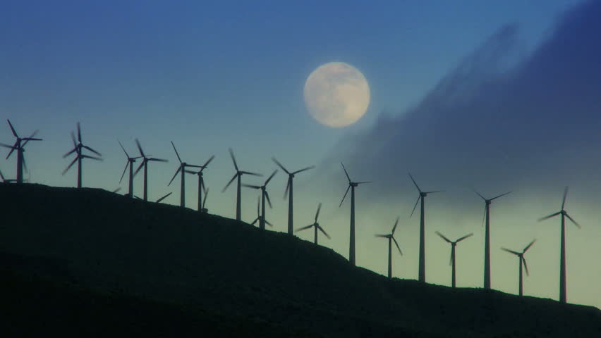 Night shot of wind turbines producing clean alternative energy in silhouette