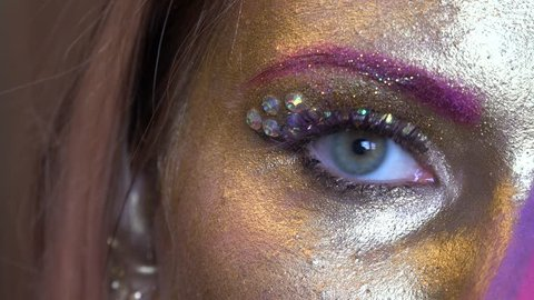 Girl's eye expression closeup with the artistic golden-purple makeup.