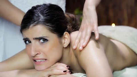 Woman making funny faces getting a very strong back massage
