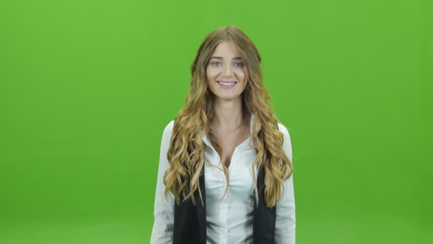 A young girl on a green background or green screen Bouncing rejoices and claps her hands as if she won