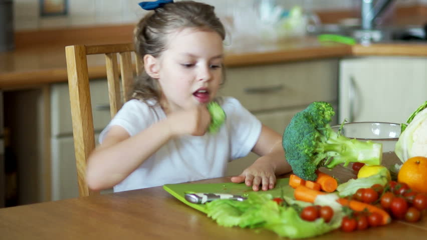 Girl eating broccoli sitting at the kitchen table. vegetarianism, healthy living,healthy vegetables, healthy food, baby food, Wellness, kitchenware, mother's assistant, food preparation | Shutterstock HD Video #25795916
