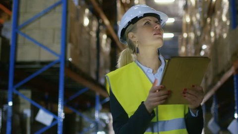 Female Surveyor Wearing Hard Hat Uses Tablet Computer for Inspection in Big Warehouse with Pallet Racks in it.