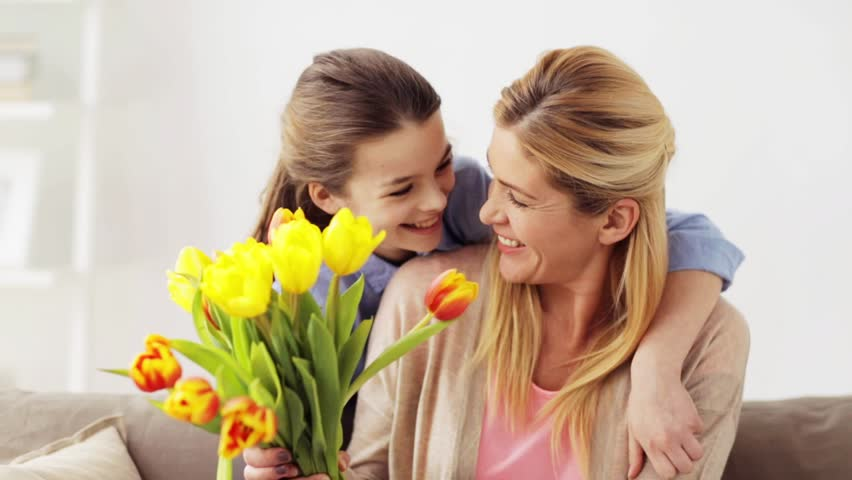 People, family, holidays and birthday concept - happy girl giving flowers and kissing he mother at home
