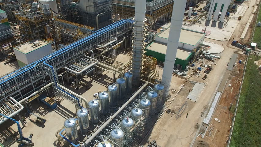 Drone flies over large metal tanks lines and high towers on oil refinery plant territory against sky with white clouds | Shutterstock HD Video #25830500