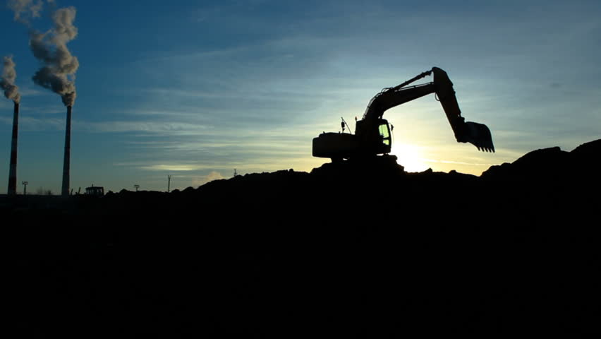 modern excavator silhouette turns pours out soil at oil refinery plant construction site against chimneys and sunlight