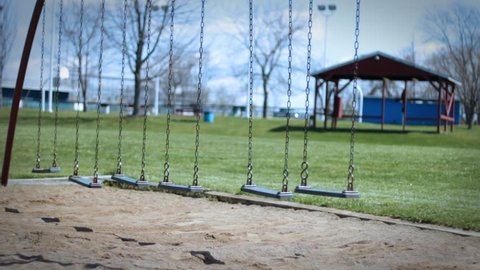 Child kidnapping concept - lonely swing flying in the wind in empty park during dreary day