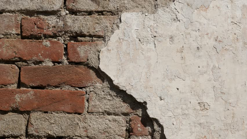 Brick wall and remains of white cement plaster slow tilt 4K 2160p 30fps UltraHD footage - Close-up of destroyed building facade 3840X2160 UHD tilting video