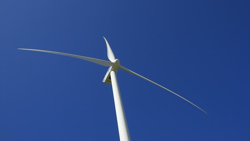 Wind turbine spinning and generating clean and sustainable power in a blue sky.